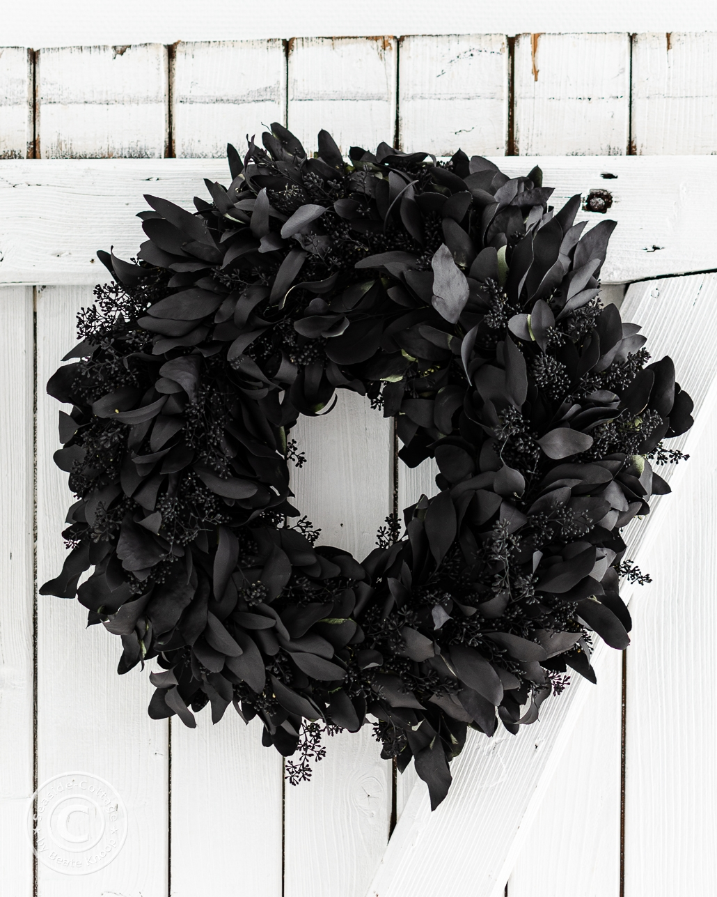 Eukalyptuskranz in Schwarz an weißer Holztür hängend