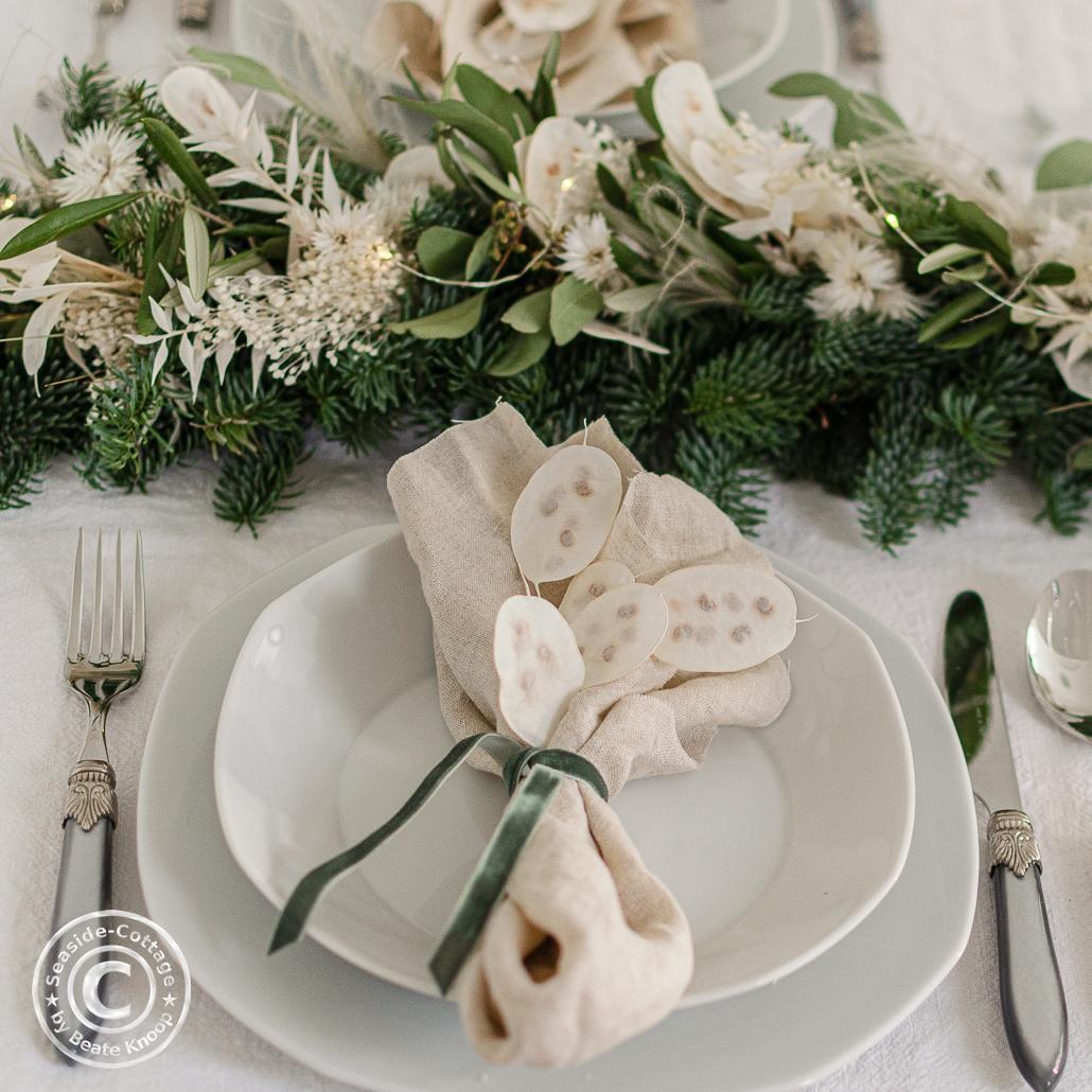Festtafel zu Weihnachten mit Trockenblumen, Eukalyptus, Olivenzweigen und Nobilistanne