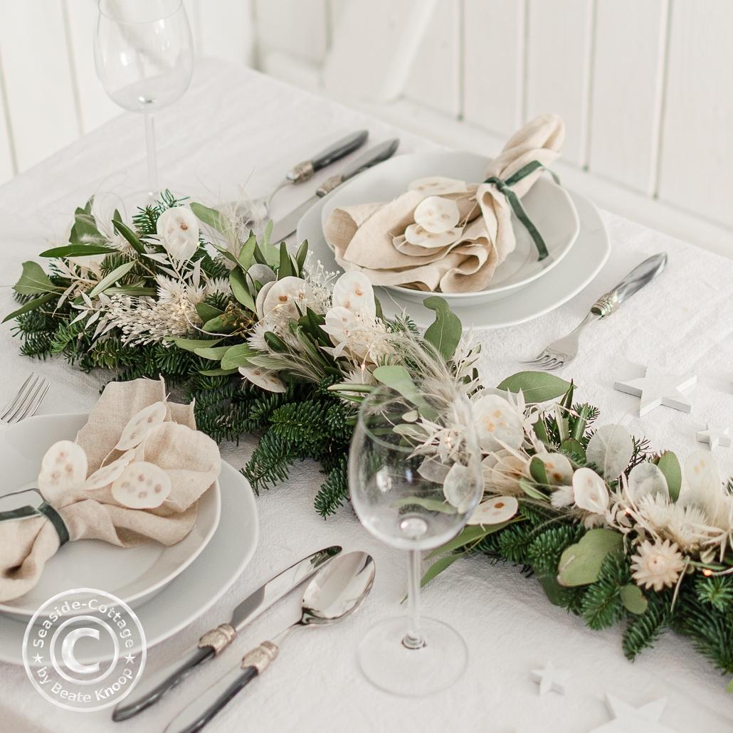 Festlich gedeckter Tisch zu Weihnachten mit Trockenblumengirlande im Bohostil
