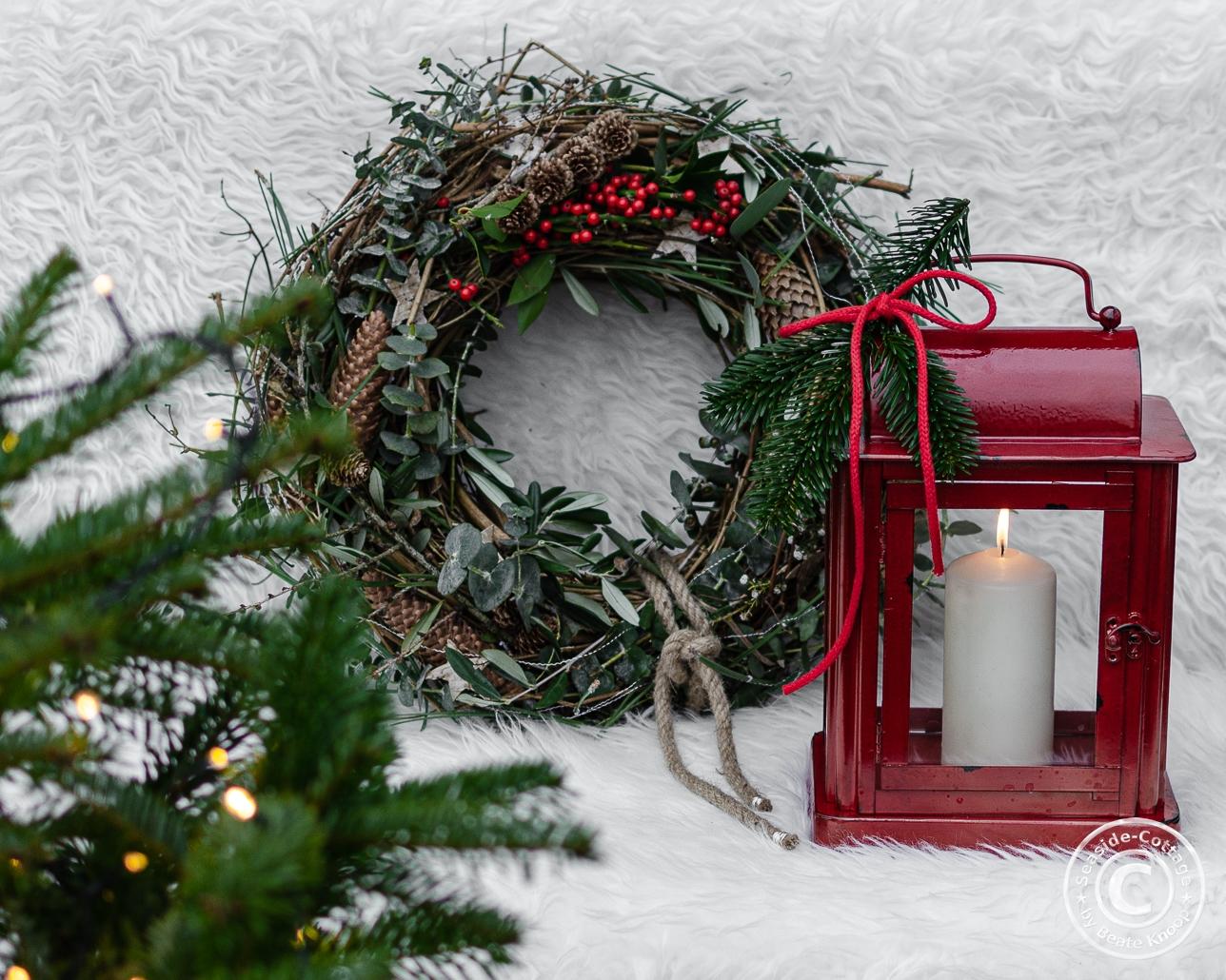 Winterdeko im Garten mit Kranz und Laterne
