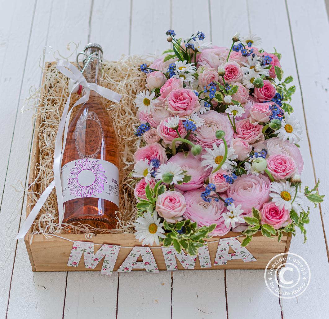 Weinkiste mit Blumen dekoriert zum Muttertag