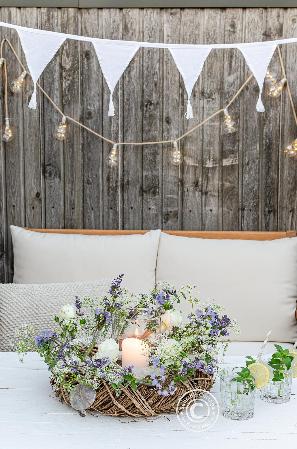 Gemütliche Sitzecke auf der Terrasse mit Sommerblumenkranz