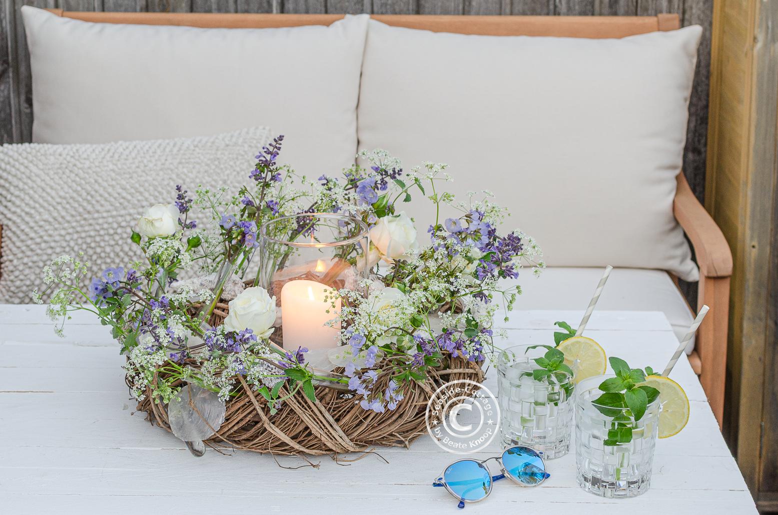 Sommerkranz mit Wiesenblumen und Windlicht als Deko für den Terrassentisch