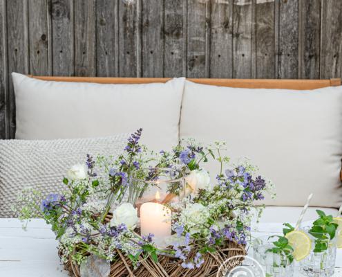 Sommerkranz mit Wiesenblumen als Tischdeko auf der Terrasse