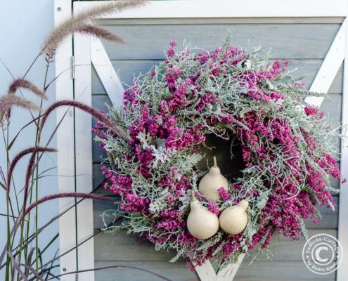 Hängender Herbstkranz mit Erica und Zierkürbissen in rosa-grau